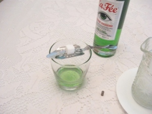 bottle of green absinthe, glass, slotted absinthe spoon, tungsten