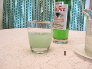 bottle of green absinthe, glass of pale green mixture, tungsten