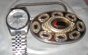 picture of wristwatch and belt buckle on miner's dinner bucket